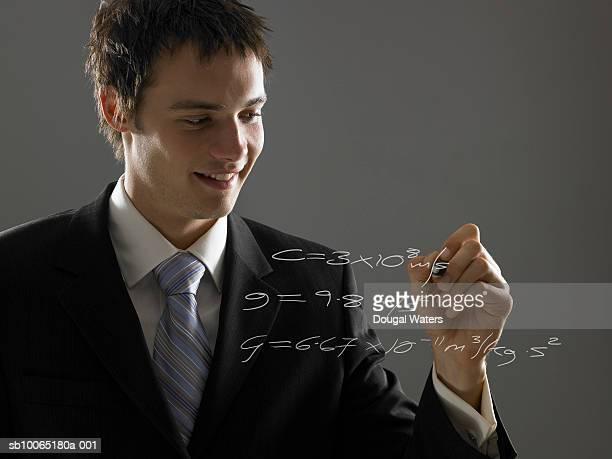 Businessman writing on transparent glass wall