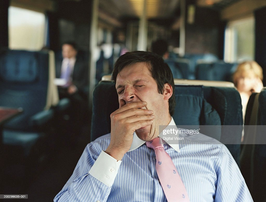 Businessman yawning on train (focus on man) : Stock Photo