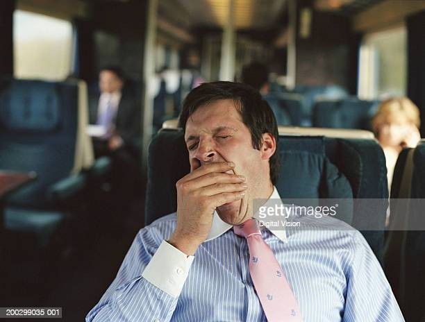 Businessman yawning on train (focus on man)