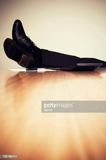 Businessman's Feet Relaxing on Desk
