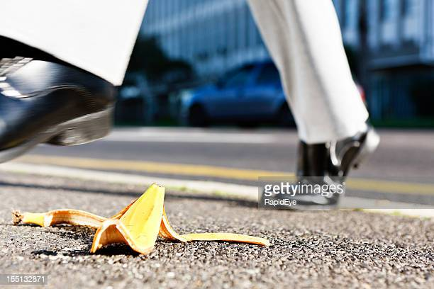 Businessman's foot moving towards banana peel on road