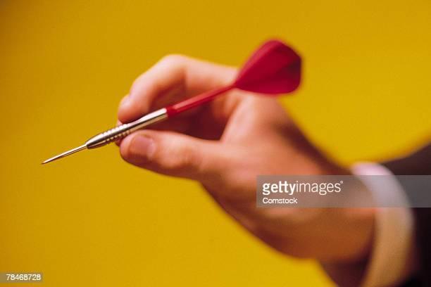 Businessman's hand aiming dart