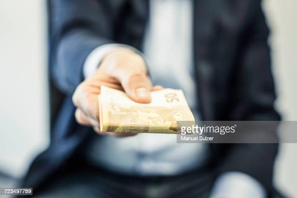 Businessmans hand handing folded fifty euro notes