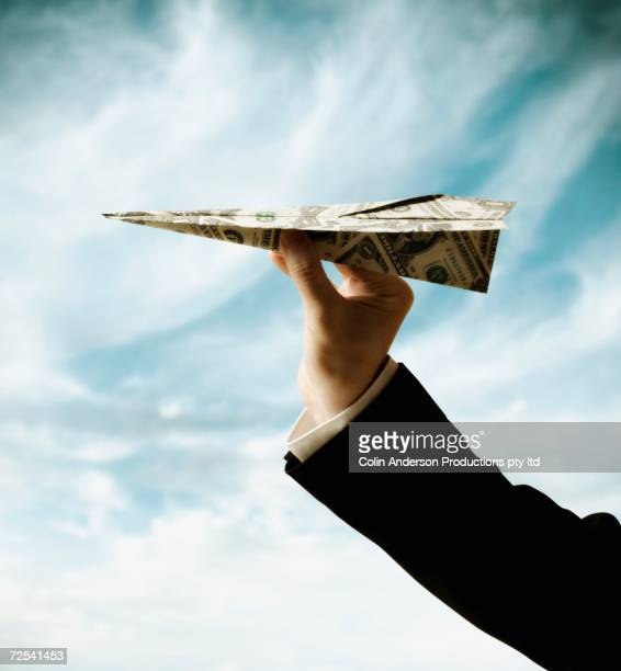 Businessman's hand holding airplane made of US Dollars