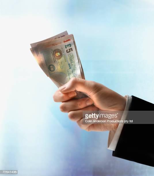 Businessman's hand holding British Pounds