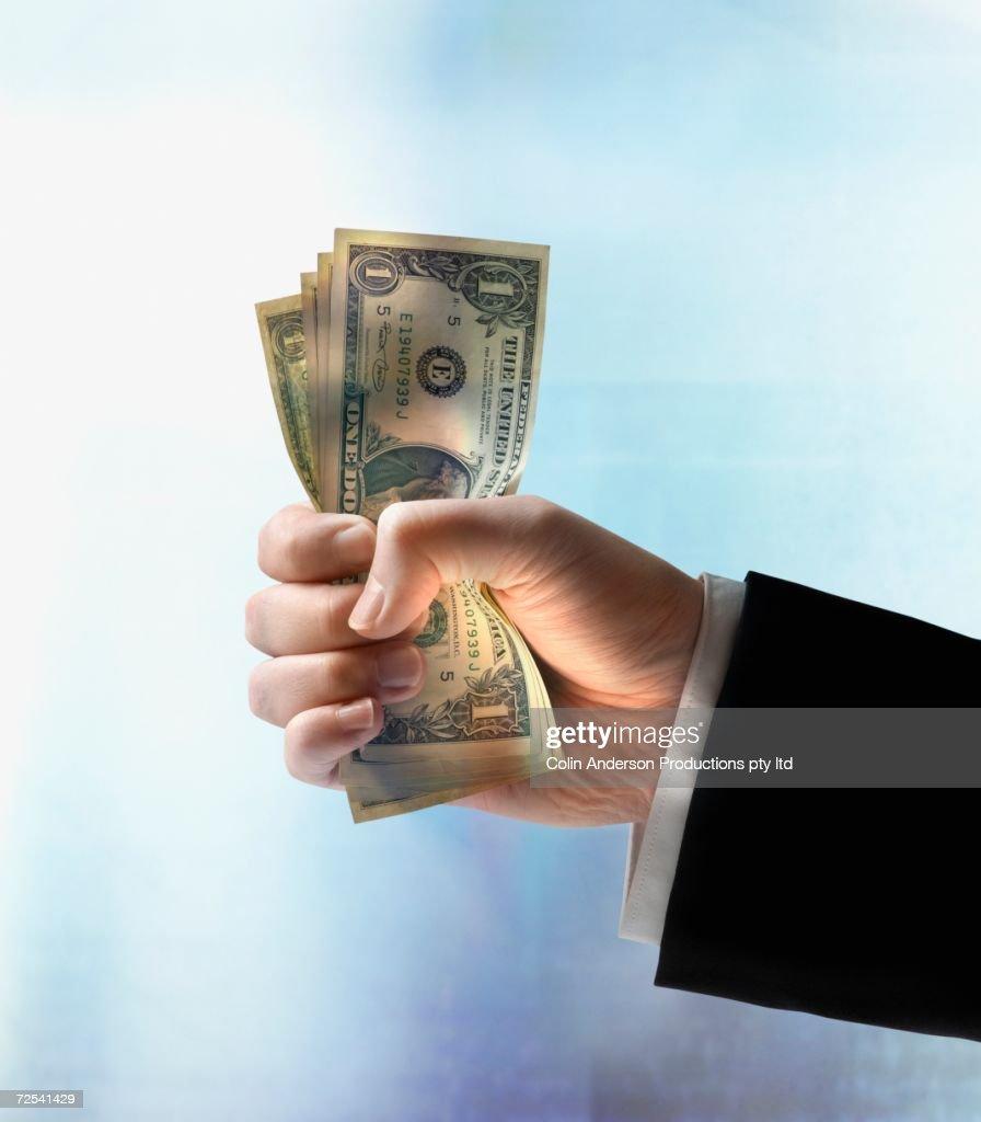 Businessman's hand holding US dollars : Stock Photo