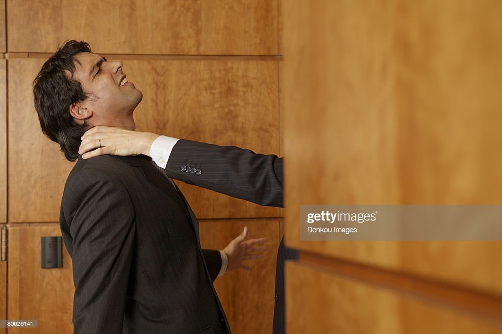 Businessman's hand strangling another businessman's neck : Stock Photo