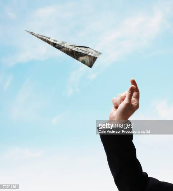 Businessman's hand throwing airplane made of US Dollars