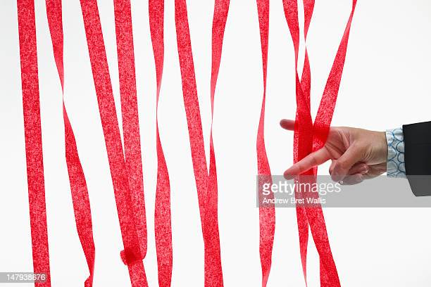 Businessman's scissor fingers cut through red tape