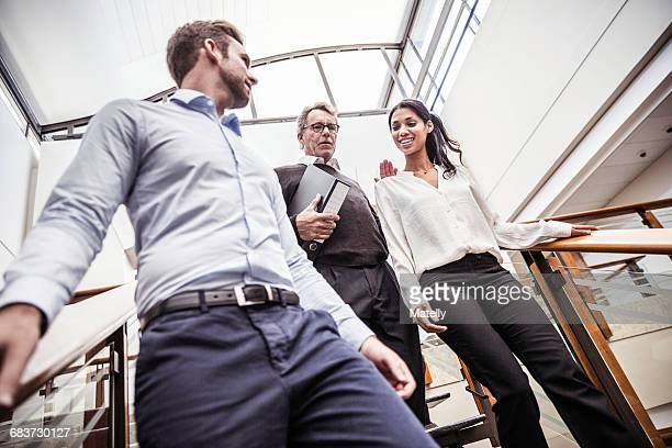 Businessmen and businesswoman having discussion moving down office stairway