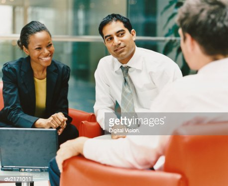 Businessmen and Businesswoman Sitting on Chairs in an Office Building Chatting : Stock Photo