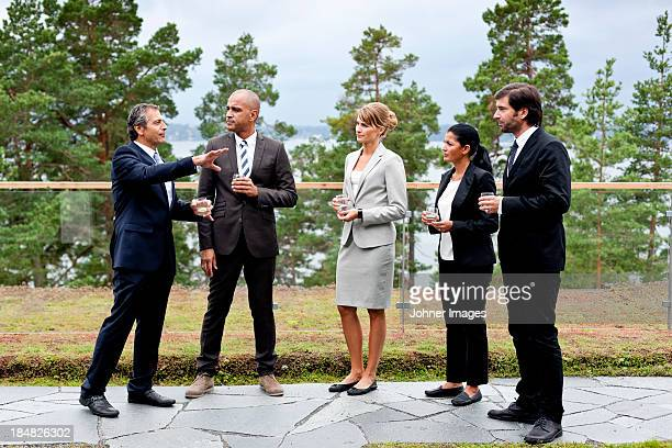 Businessmen and businesswomen discussing outdoors