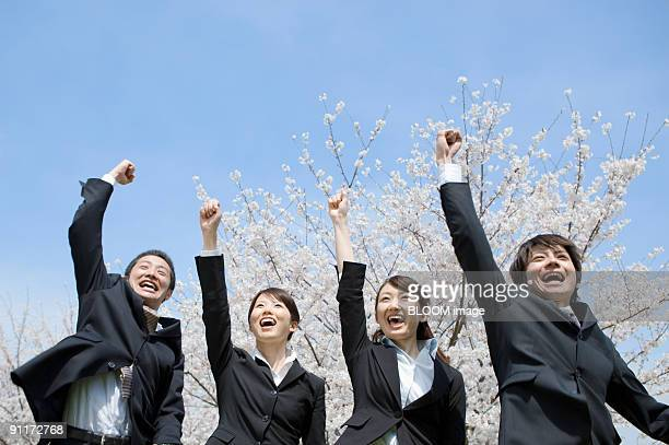 Businessmen and businesswomen smiling, holding fists in the air