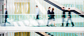 Group of business people walking on a raised platform in a modern office corridor, full of glass. Blurred motion.