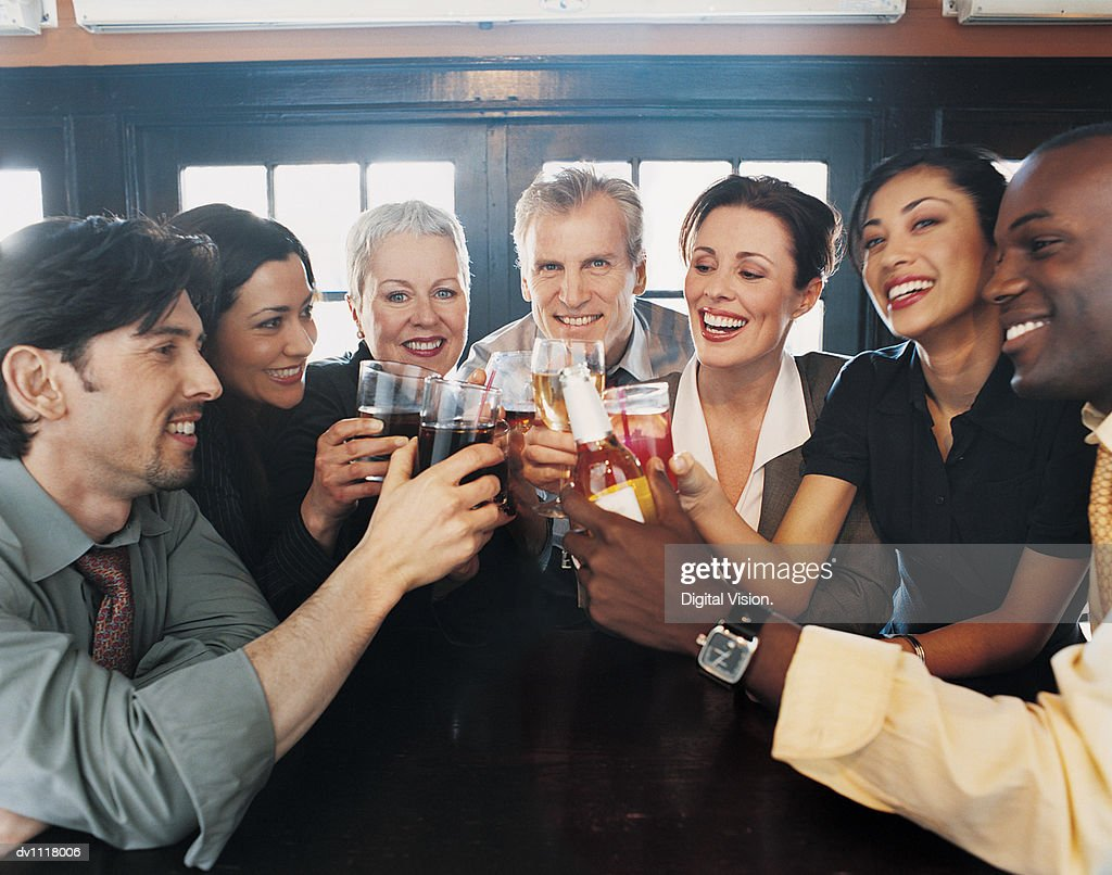 Businessmen and Businesswomen Work Colleagues Toasting in a Bar