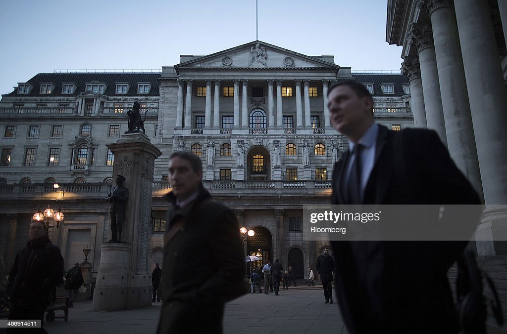 Businessmen and pedestrians walk past the Bank of England in London, U.K., on Tuesday, Feb. 4, 2014. Between 2007 and 2011, policy makers in London lagged behind their American counterparts in cutting rates and adopting emergency policy measures in response to the financial crisis. Photographer: Simon Dawson/Bloomberg via Getty Images