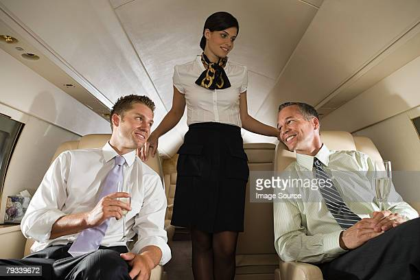 Businessmen and stewardess on jet