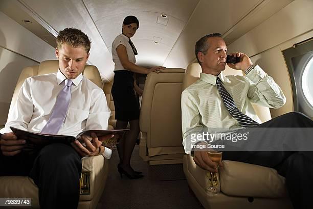Hommes d'affaires et hôtesse sur jet