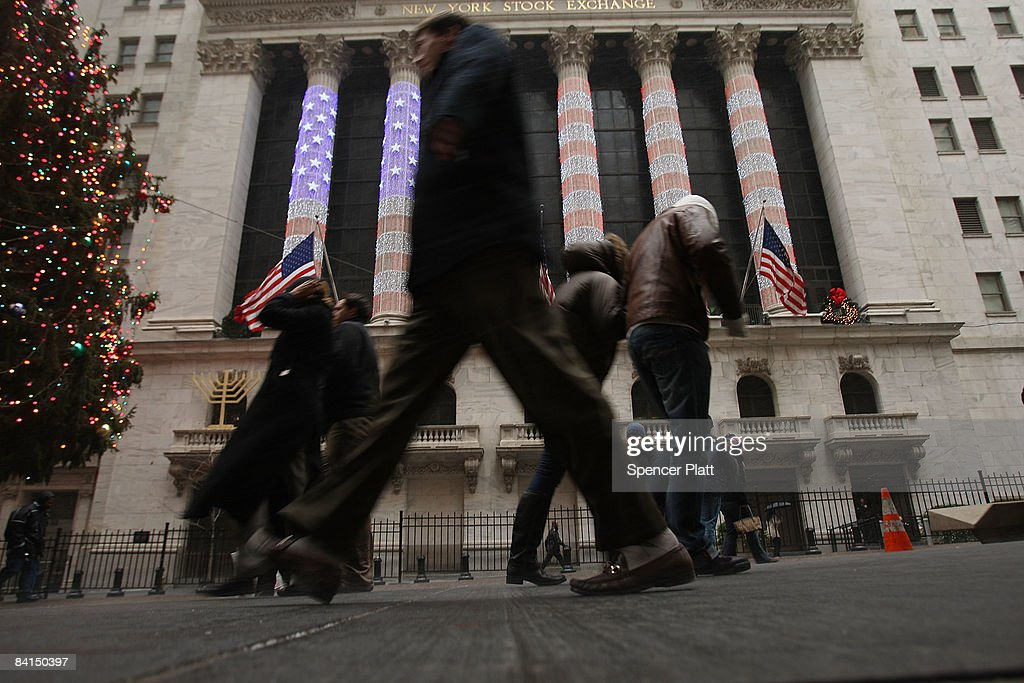 Businessmen and tourists walk by the New York Stock Exchange (NYSE) December 31, 2008 in New York City. Wednesday is the last day of trading on the exchange in what has been one of the most tumultuous years in finance in the nation's history.