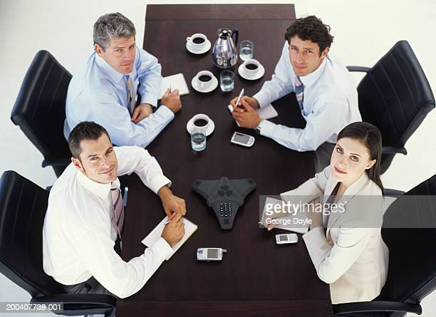 Businessmen and woman at conference table, portrait, elevated view