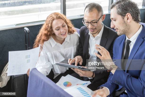 Businessmen and woman looking at digital tablet on passenger ferry