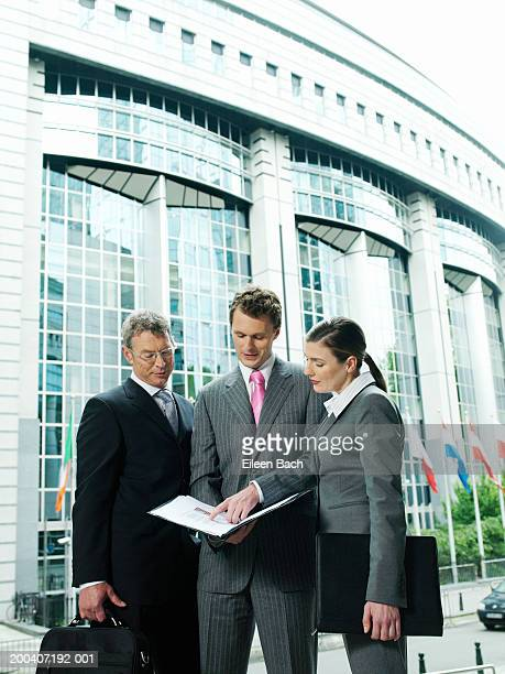 Businessmen and woman looking at paperwork outdoors, low angle view