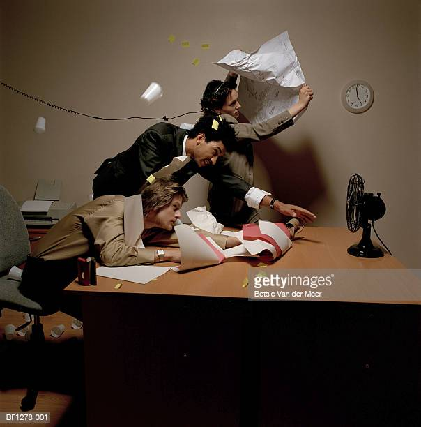 Businessmen and woman reaching to turn off fan, papers flying