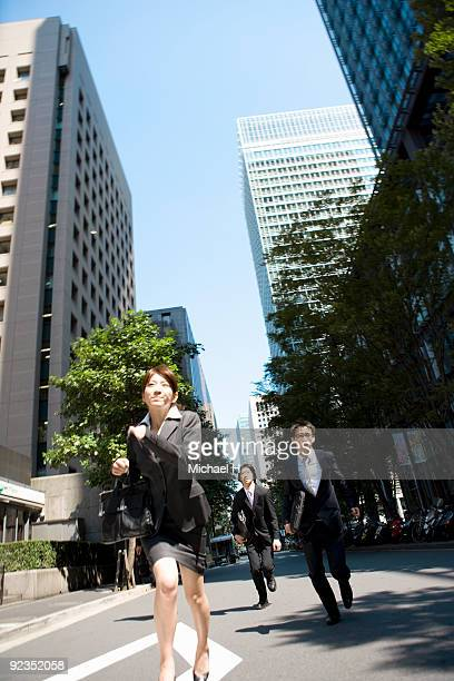 Businessmen and woman running on street