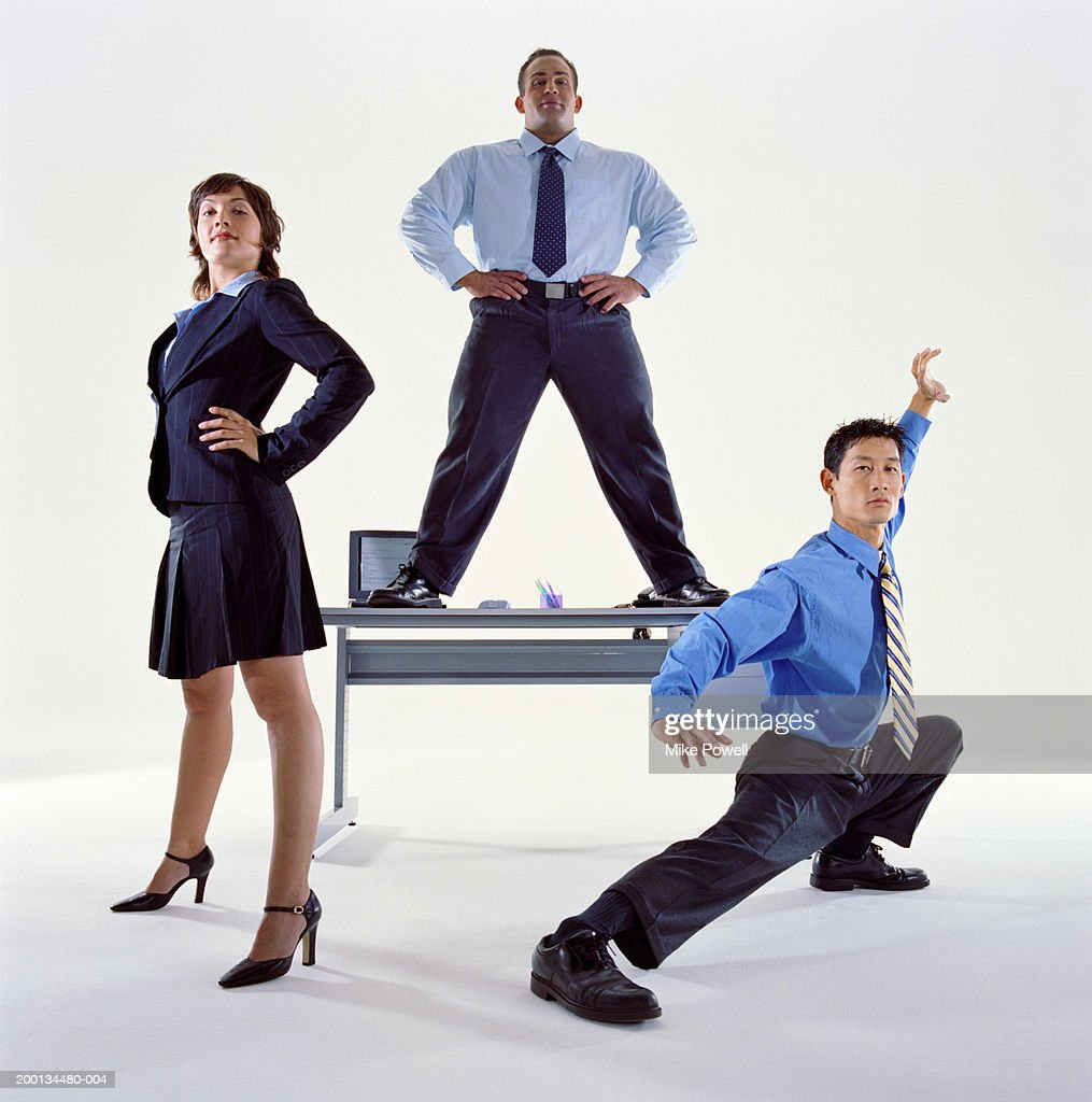 Businessmen and woman standing by desk, one man in karate pose