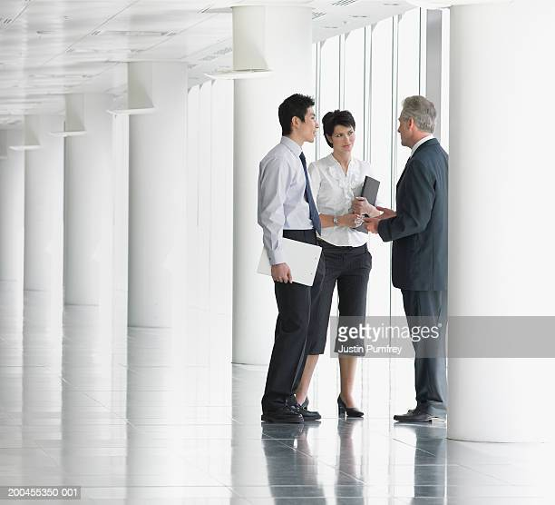 Businessmen and woman standing by pillar and window talking