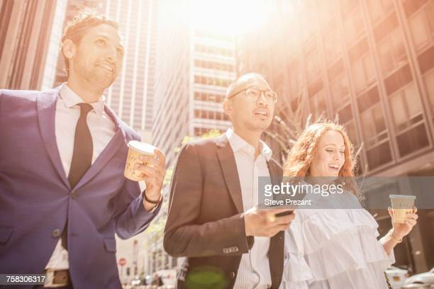 Businessmen and woman strolling along city sidewalk, New York, USA