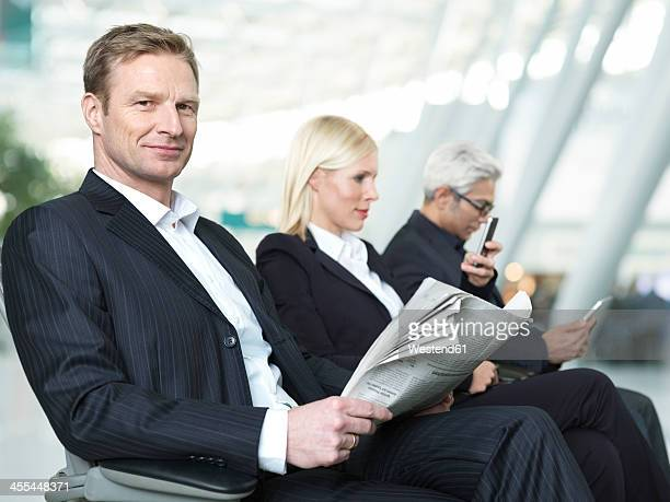 Businessmen and woman waiting at airport