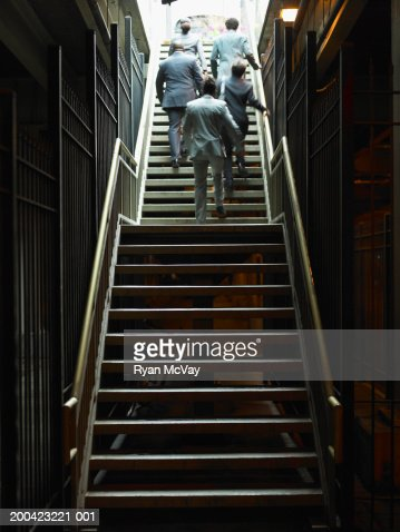 Businessmen and woman walking up subway stairs, rear view : Stock Photo