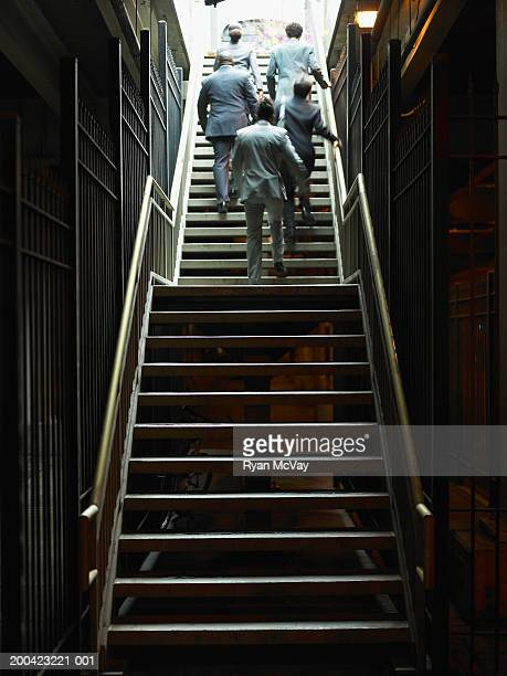 Businessmen and woman walking up subway stairs, rear view
