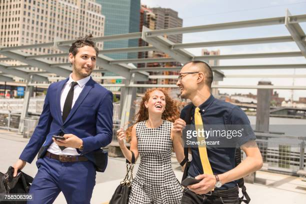 Businessmen and woman with luggage walking and talking on waterfront, New York, USA