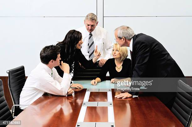 Businessmen and women arguing at a meeting