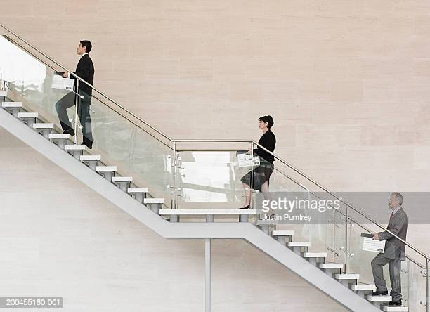 Businessmen and women carrying boxes up stairs, side view