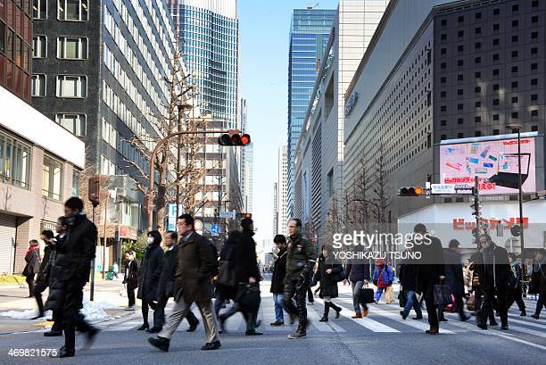 Businessmen and women cross a road in Tokyo on February 17 2014 Japan's economy logged its best performance in three years as Premier Shinzo Abe's...