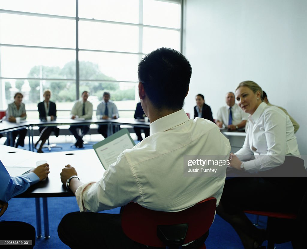 Businessmen and women in meeting at circular table : Stock Photo