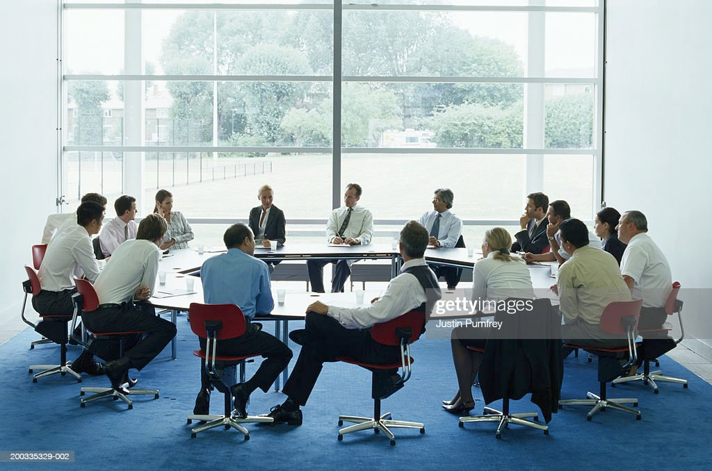 Businessmen and women in meeting at large circular table : Stock Photo