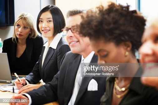 Businessmen and women in meeting, close-up