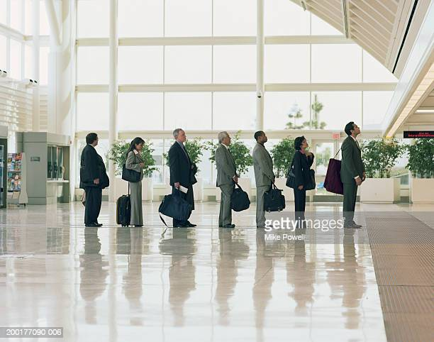 Businessmen and women lining up in airport