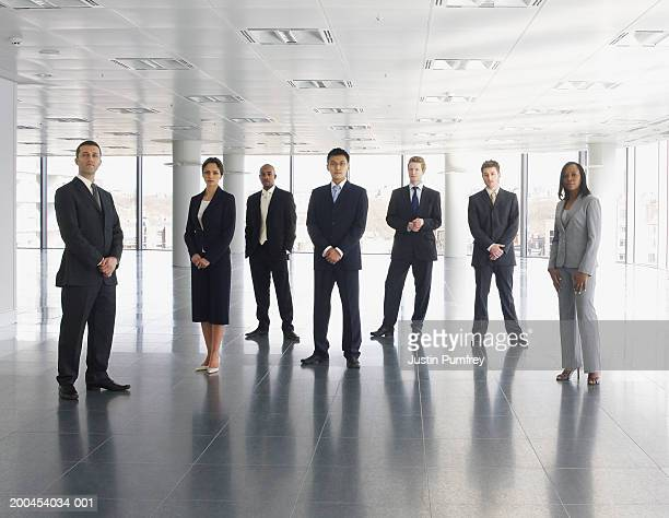 Businessmen and women standing in empty office space, portrait