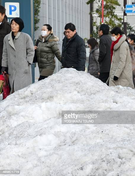 Businessmen and women walk on a street while a mount of snow remains on the shoulder of a road in Tokyo on February 17 2014 Japan's economy logged...