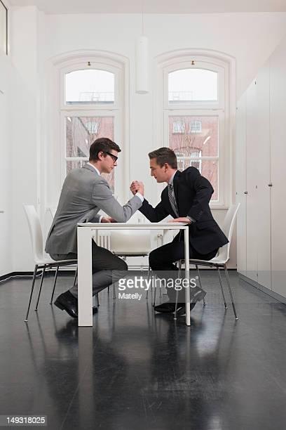 Businessmen arm wrestling in office