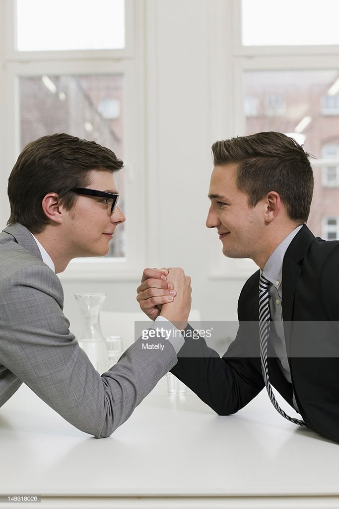 Businessmen arm wrestling in office : Stock Photo