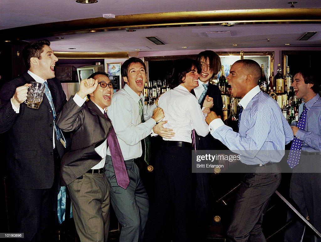 Businessmen at bar cheering