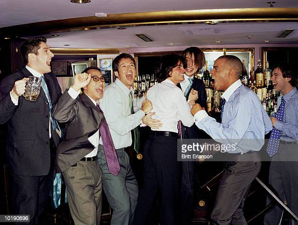 Businessmen at bar cheering