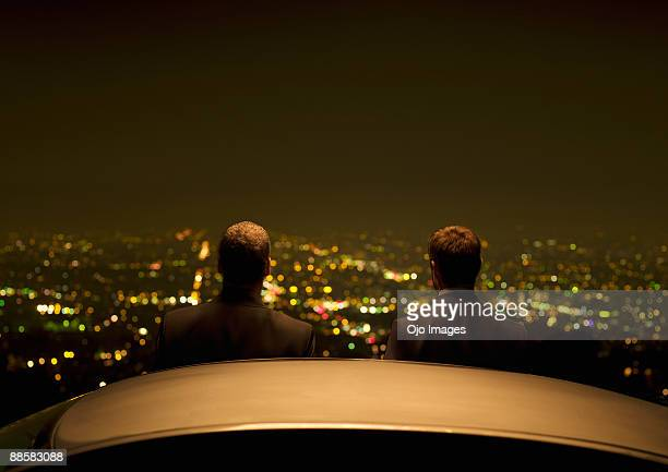 Businessmen at city overlook at night