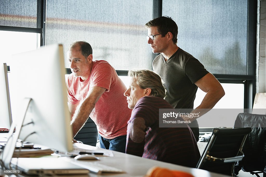 Businessmen at computer in startup office